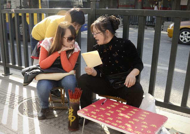(File) A fortune-teller talks with two girls by a road in Beijing on October 24, 2012