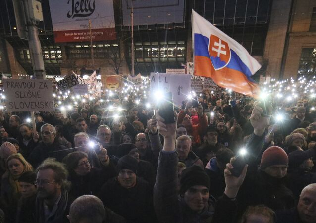 Demonstrators light with the torches of their smartphones during an anti-government rally in Bratislava, Slovakia, Friday, March 9, 2018. The country-wide protests demand a thorough investigation into the shooting deaths of Jan Kuciak and Martina Kusnirova, whose bodies were found in their home on Feb. 25, and also demand changes in the government.