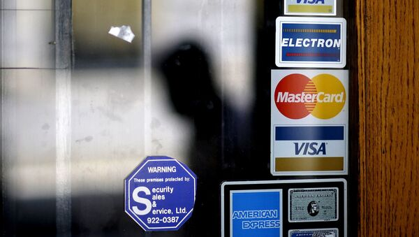 In this July 18, 2012, file photo, a pedestrian walks past credit card logos posted on a downtown storefront in Atlanta. After a stint of frugality, Americans have returned to their borrowing ways. But are they getting into the kinds of debt trouble that lead to recessions? In 2017, U.S. consumers now owe roughly $12.73 trillion to banks and other lenders for mortgages, car loans and credit card spending, according to the New York Federal Reserve. That exceeds even the total before the last financial crisis. - Sputnik International