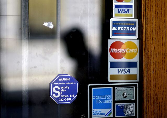 In this July 18, 2012, file photo, a pedestrian walks past credit card logos posted on a downtown storefront in Atlanta. After a stint of frugality, Americans have returned to their borrowing ways. But are they getting into the kinds of debt trouble that lead to recessions? In 2017, U.S. consumers now owe roughly $12.73 trillion to banks and other lenders for mortgages, car loans and credit card spending, according to the New York Federal Reserve. That exceeds even the total before the last financial crisis.
