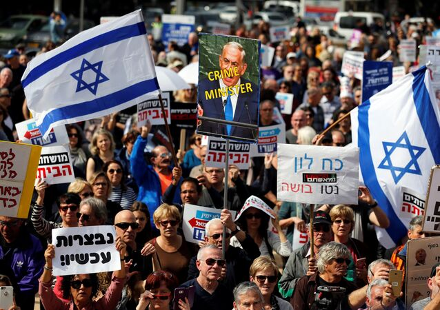 Protesters hold signs calling upon Israeli Prime Minister Benjamin Netanyahu to step down during a rally in Tel Aviv, Israel February 16, 2018