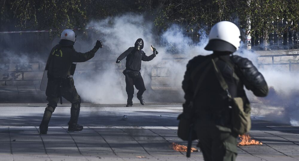 A masked protester throws a molotov cocktail at riot policemen during clashes outside the University of Thessaloniki campus, in Thessaloniki, Greece Saturday March 10, 2018