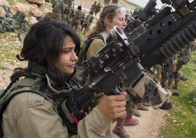 Israeli soldiers from the mixed-gender Lions of the Jordan battalion, under the Kfir Brigade, check their weapons at the end of the last training before being assigned their posting, on February 28, 2017, near the West Bank village of Bardale, east of Jenin