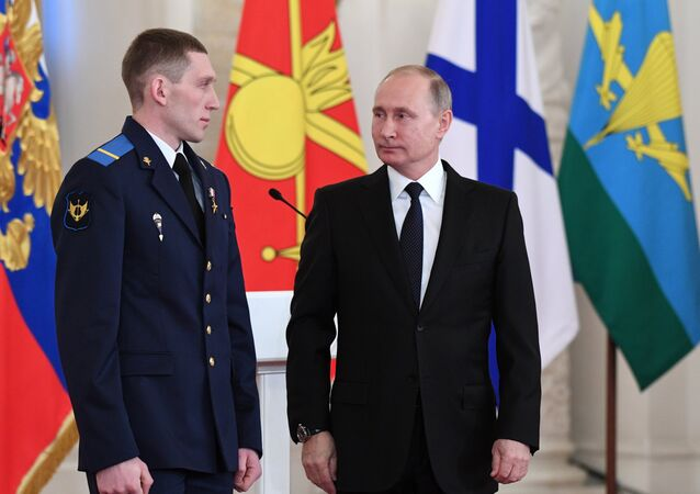 President Vladimir Putin and Gefr. Denis Portnyagin, left, at a ceremony to present state awards to the Russian service personnel who took part in the counter-terrorism operation in the Syrian Arab Republic. File photo