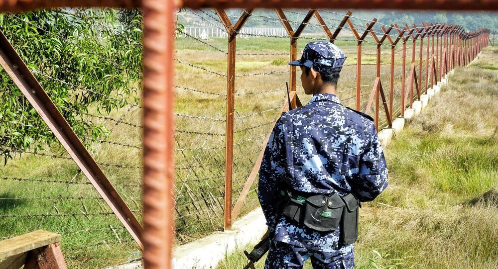 A Myanmar border guard stands next to fencing in a field on the outskirts of Maungdaw in Rakhine state on January 24, 2018