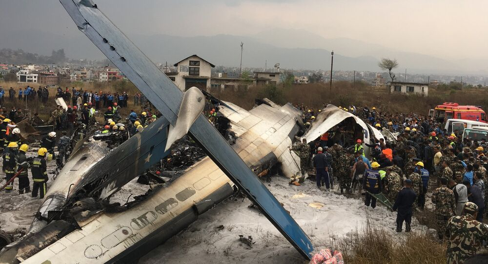 Nepalese rescuers stand near a passenger plane from Bangladesh that crashed at the airport in Kathmandu, Nepal, Monday, March 12, 2018