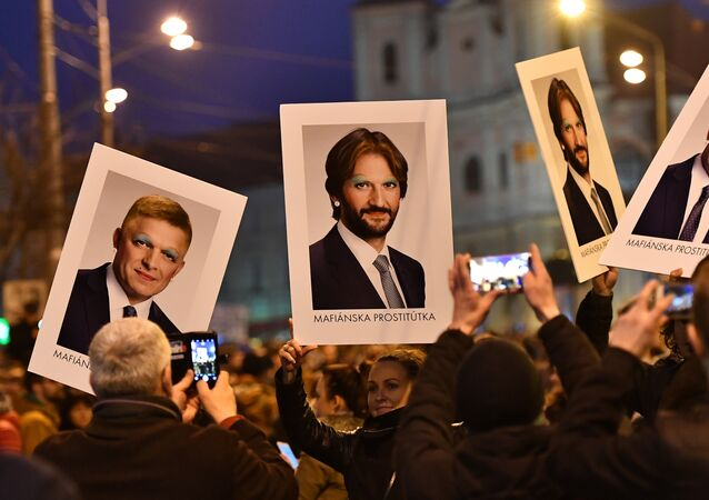 Protesters holds placards bearing faceted portraits of Slovakia's Prime Minister Robert Foco and Foreign Minister Robert Kalinak during a rally under the slogan For a Decent Slovakia, against corruption and to pay tribute to murdered Slovak journalist Jan Kuciak and his fiancee Martina Kusnirova on March 9, 2018 at the Slovak National Uprising (SNP) square in Bratislava, Slovakia