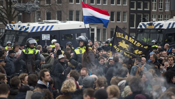(File) A flag reads Islamists Not Welcome as mounted Dutch riot police separates pro and anti Pegida demonstrators during a rally against islamisation in Amsterdam, Netherlands, Saturday, Feb. 6, 2016 - Sputnik International