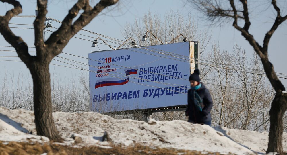 A woman walks past a billboard advertising the upcoming presidential election, in Krasnoyarsk, Russia March 11, 2018