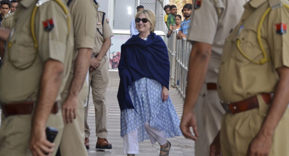 In this Thursday, March 15, 2018 photo, former U.S. Secretary of State Hillary Clinton, center, arrives at the departure terminal of Jodhpur airport in Rajasthan state, India