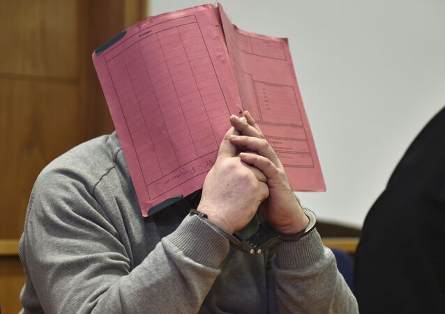 In this Feb. 26, 2015 file photo former nurse Niels Hoegel., accused of multiple murder and attempted murder of patients, covering his face with a file at the district court in Oldenburg, Germany
