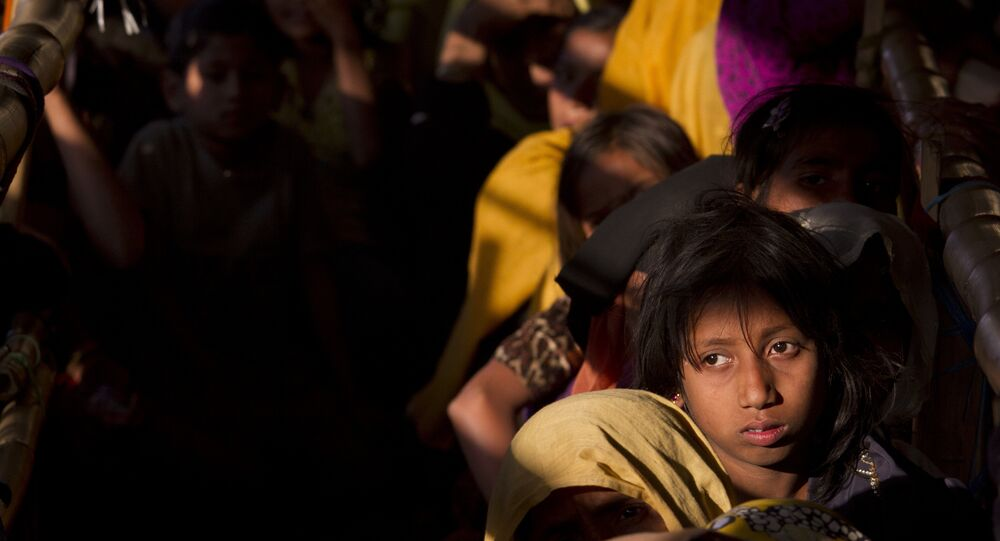 Rohingya refugees wait in a queue to receive relief material at the Balukhali refugee camp near Cox's Bazar, Bangladesh, Saturday, Jan. 27, 2018