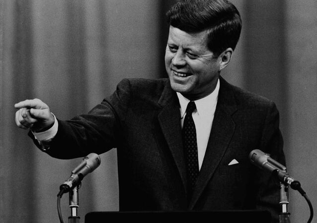 President Kennedy broke up the serious trend of his news conference with a grin as he commented on a question about tax cuts in 1963
