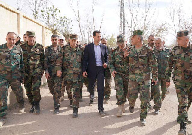 Syrian President Bashar al-Assad walks with Syrian army soldiers in eastern Ghouta, Syria, March 18, 2018