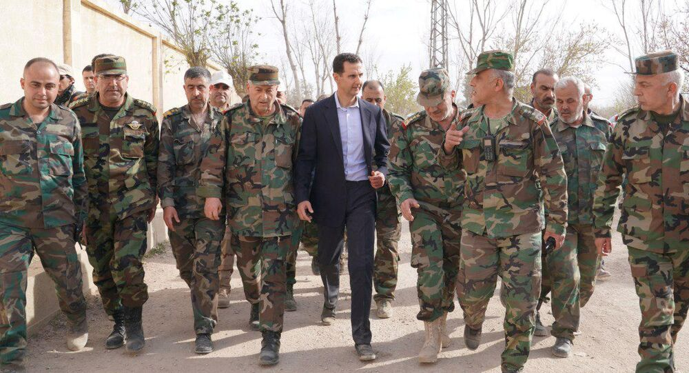 Syrian President Bashar al-Assad walks with Syrian army soldiers in eastern Ghouta, Syria, March 18, 2018