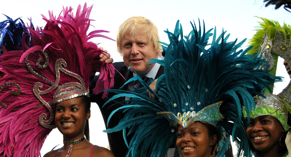 Mayor of London, Boris Johnson (2nd L) poses with costumed masqueraders from the Genesis Mas band in London, on August 24, 2011, ahead of the Notting Hill Carnival