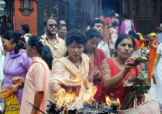 Hindu devotees offer oil and butter to lamps during ritual prayers at Kumbheswore temple in Patan, on the outskirts of Kathmandu. (File)