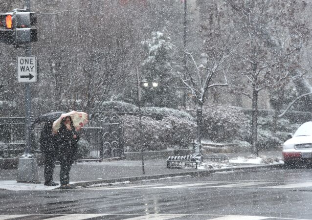Pedestrians weather the latest storm to hit the US east coast on March 21, 2018, in Washington, DC