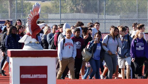 Students walk out of Marjory Stoneman Douglas High School as part of a National School Walkout to honor the 17 students and staff members killed at the school in Parkland, Florida, U.S., March 14, 2018. - Sputnik International