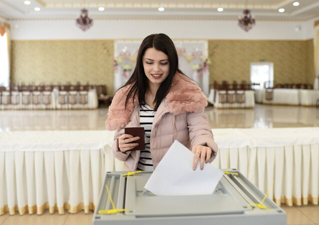 A girl puts her ballot into the box at a polling station in Bakhchysarai during the Russian presidential election.