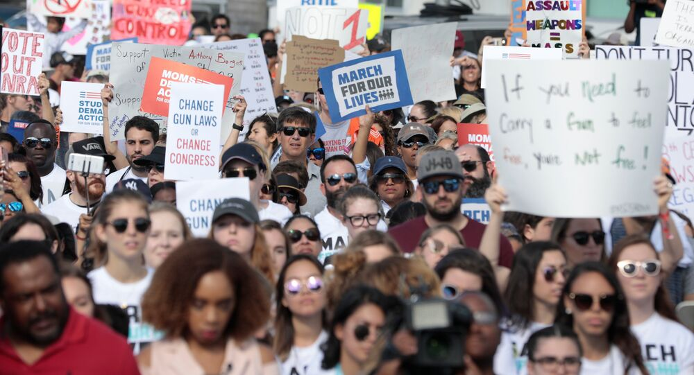 People and students hold signs while rallying in the street during the March for Our Lives demanding stricter gun control laws at the Miami Beach Senior High School, in Miami, Florida, U.S