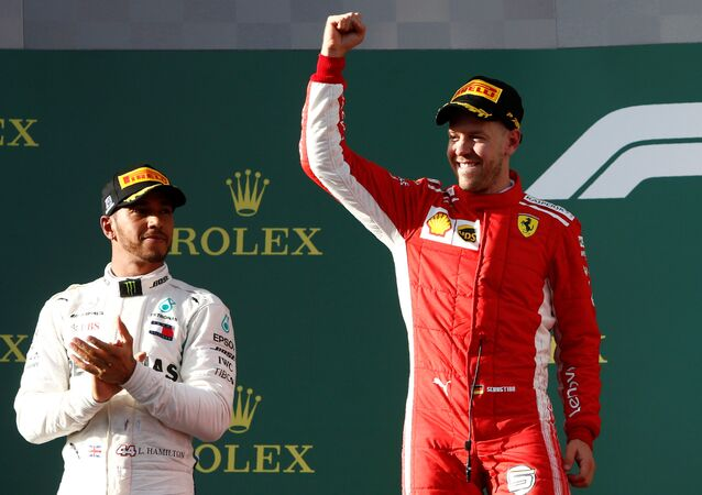 Formula One F1 - Australian Grand Prix - Melbourne Grand Prix Circuit, Melbourne, Australia - March 25, 2018 Ferrari's Sebastian Vettel celebrates his win on the podium with Mercedes' Lewis Hamilton