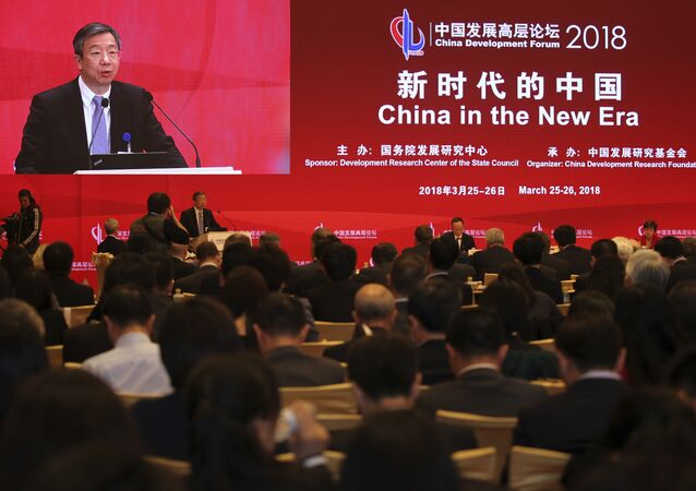 China's Central Bank Governor Yi Gang delivers a speech at the China Development Forum at the Diaoyutai State Guesthouse in Beijing, Sunday, March 25, 2018