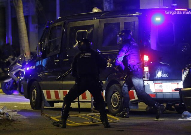 Catalan Mossos d'Esquadra regional police officers run by a police van after metal raining were thrown during a protest after the detention of deposed leader of Catalonia's pro-independence party Carles Puigdemont in Barcelona, Spain, Sunday, March 25, 2018. Puigdemont was arrested Sunday by German police on an international warrant as he tried to enter the country from Denmark.