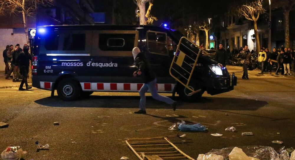 A protestor throws a barrier at a Catalan police van during skirmishes after former regional president Carles Puigdemont was detained in Germany, at a demonstration in Barcelona, Spain March 25, 2018.