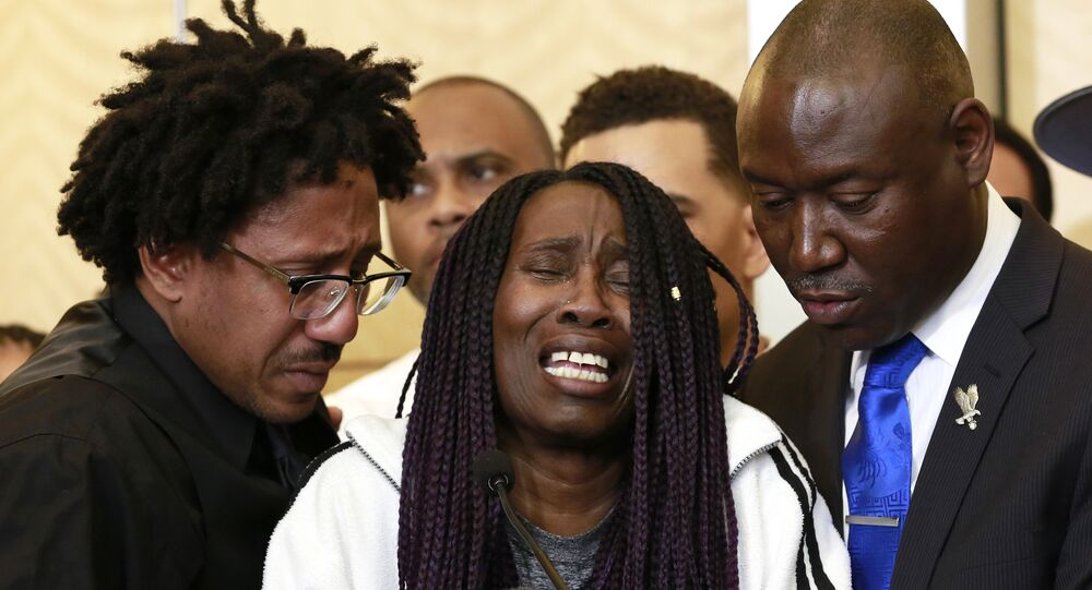 A tearful Sequita Thompson, center, discusses the shooting of her grandson, Stephon Clark, during a news conference, Monday, March 26, 2018, in Sacramento, Calif. Clark, who was unarmed, was shot and killed by Sacramento police officers who were responding to a call about person smashing car windows a week ago.