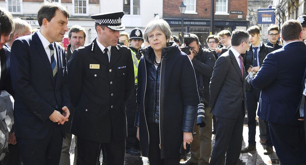 Britain's Prime Minister Theresa May, centre, is briefed by members of the police as she views the area where former Russian double agent Sergei Skripal and his daughter were found critically ill, in Salisbury, England, Thursday, March 15, 2018
