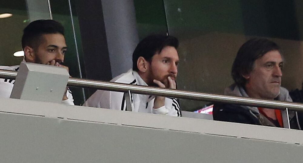 Argentina's Lionel Messi, center, watches from the tribune during the international friendly soccer match between Spain and Argentina at the Wanda Metropolitano stadium in Madrid, Spain, Tuesday March 27, 2018