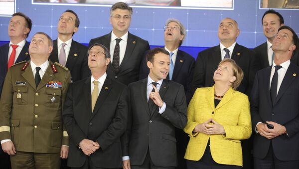 French President Emmanuel Macron, front center, speaks with German Chancellor Angela Merkel, front second right, as they look up at a drone flying above their heads during a group photo at an EU summit at the Europa building in Brussels on Thursday, Dec. 14, 2017 - Sputnik International