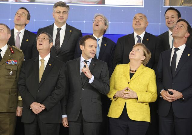 French President Emmanuel Macron, front center, speaks with German Chancellor Angela Merkel, front second right, as they look up at a drone flying above their heads during a group photo at an EU summit at the Europa building in Brussels on Thursday, Dec. 14, 2017