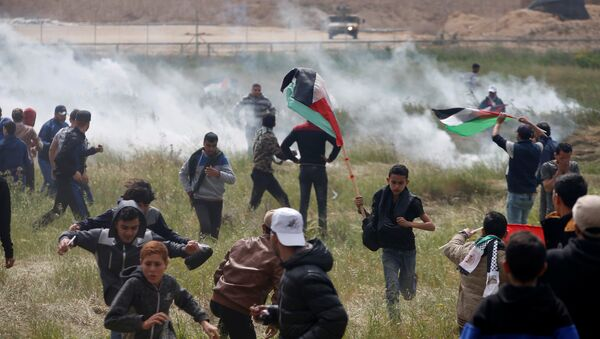 Palestinians run from tear gas fired by Israeli troops during clashes, during a tent city protest along the Israel border with Gaza, demanding the right to return to their homeland, east of Gaza - Sputnik International