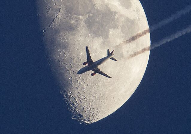 An aircraft passes the moon over Frankfurt, Germany