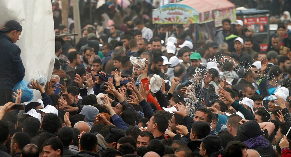 Palestinians receive food during a tent city protest along the Israel border with Gaza, demanding the right to return to their homeland, east of Gaza City