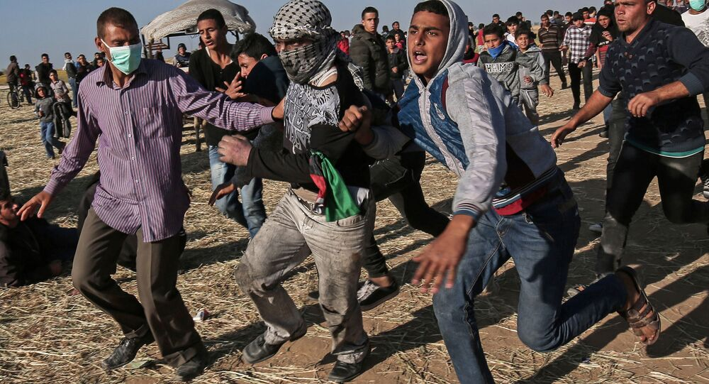 Protesters run during clashes with Israeli security forces following a demonstration near the border with Israel, east of Khan Yunis, in the southern Gaza Strip