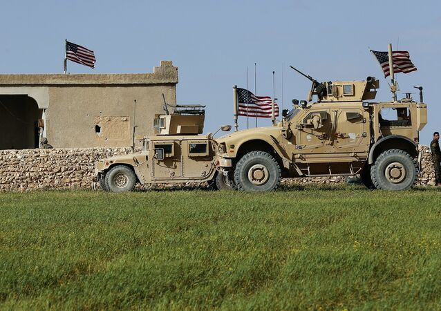 In this picture taken Thursday, March 29, 2018, U.S. soldiers, left, sit on a house that turned to an outpost on a road leading to the tense front line between U.S-backed Syrian Manbij Military Council fighters and Turkish-backed fighters, at Halawanji village, north of Manbij town, Syria