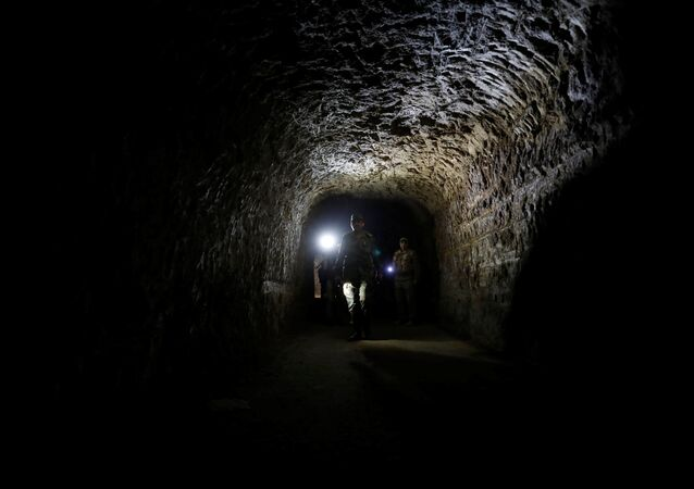 A member of Syrian forces of President Bashar al Assad walks inside a tunnel that was used by rebels in Jobar, eastern Ghouta, in Damascus, Syria April 2, 2018