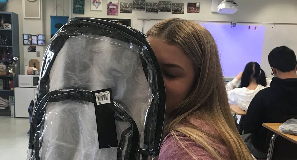 A Marjory Stoneman Douglas High School student poses with a clear backpack, provided to her as a new security measure, in Parkland, Florida, U.S., April 2, 2018 in this image obtained from social media