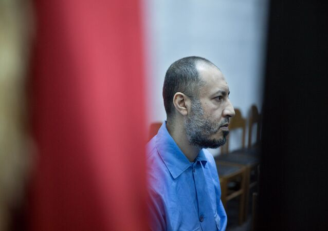 Saadi Muammar Gadhafi, wears a blue jumpsuit behind bars during his trial in the center of Tripoli, Libya, Sunday, Nov. 1, 2015.