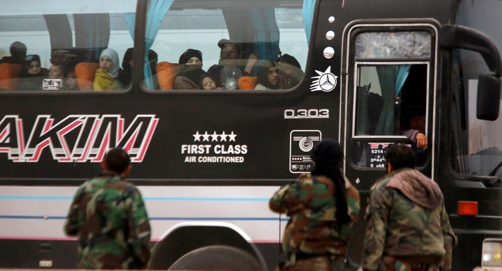 Syrian rebels and civilians look through a bus window as they leave Harasta in eastern Ghouta, in Damascus, Syria March 23, 2018