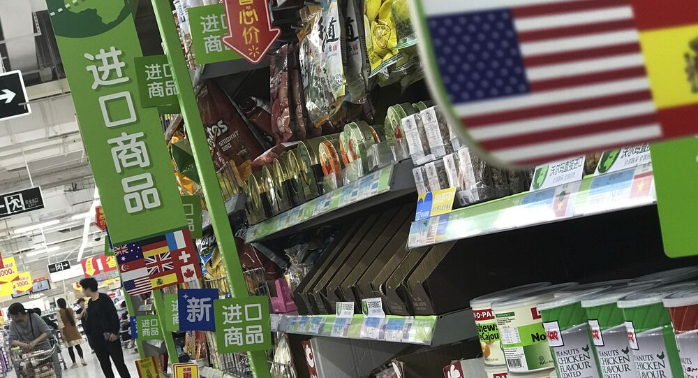 Women push a shopping cart near nuts and sweets imported from the United States and other countries displayed on a section selling imported foods at a supermarket in Beijing, Monday, April 2, 2018