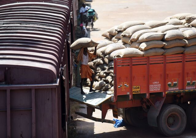 An Indian labourer loads grain sakcs on to a truck at a railway goods yard in Chennai on August 3, 2016