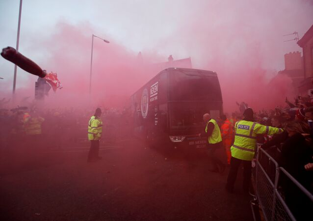 Liverpool fans set off flares and throw missiles at the Manchester City team bus outside the stadium before the match.