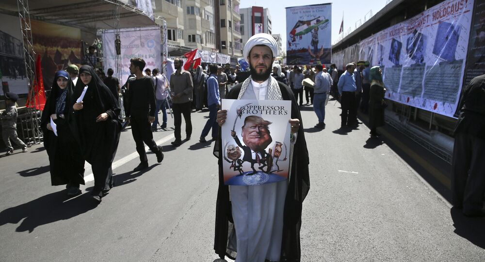 A clergyman holds a poster showing caricatures of U.S. President Donald Trump, center, Israeli Prime Minister Benjamin Netanyahu, left, and Saudi Arabia's King Salman in an annual pro-Palestinian rally marking Al-Quds (Jerusalem) Day in Tehran, Iran, Friday, June 23, 2017
