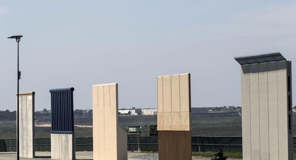 A US border patrol quad is seen next to US President Donald Trump's border wall prototypes from Tijuana, northwestern Mexico