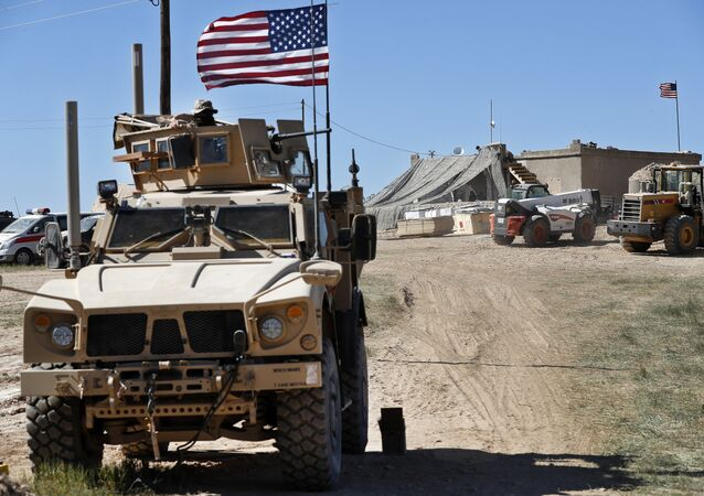 A US soldier, left, sits on an armored vehicle behind a sand barrier at a newly installed position near the tense front line between the US-backed Syrian Manbij Military Council and the Turkish-backed fighters, in Manbij, northern Syria, April 4, 2018