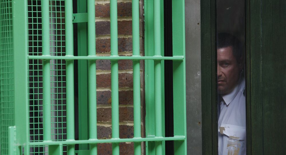Under the watchful eye of prison security personnel, Britain's Prince Charles, not seen, tours Belmarsh prison, in southeast London, Thursday Sept. 10, 2009.